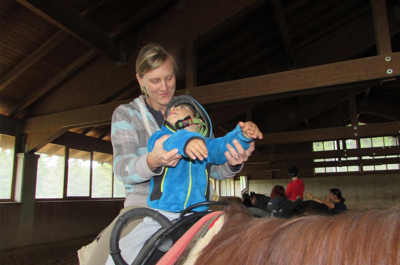 Istruttrice e bambino a cavallo, ippoterapia